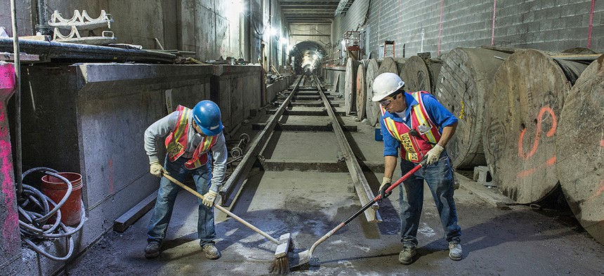 Construction workers sweep at the second avenue subway line