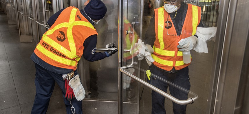 MTA workers disinfecting touch points