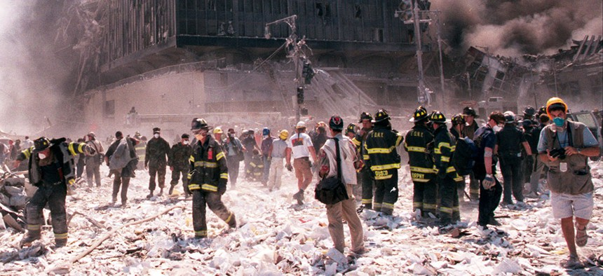 New York City firefighters and journalists stand near the area known as Ground Zero after the collapse of the Twin Towers.