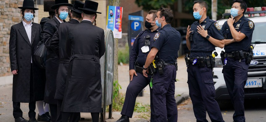 NYPD officers talk to members of the Orthodox community in Borough Park on October 7th.