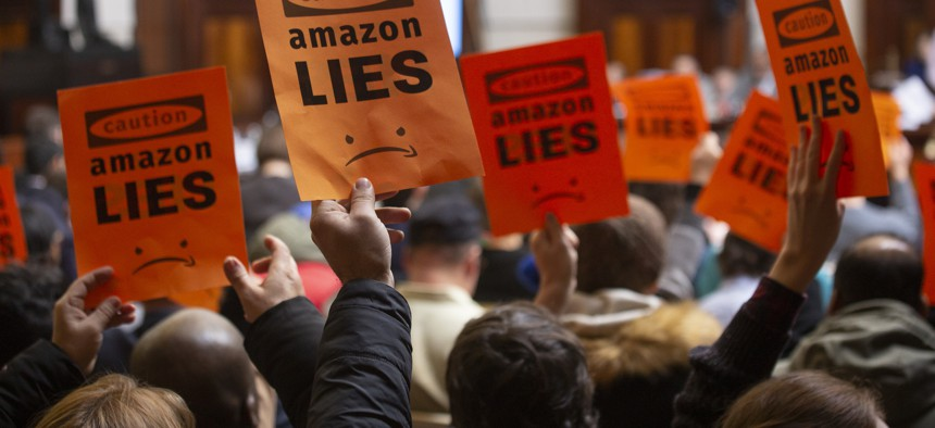 Protesters hold up signs at the second New York City Council hearing on Amazon's planned headquarters in Queens.
