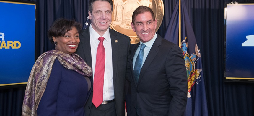 State Senate Majority Leader Andrea Stewart-Cousins smiles alongside Gov. Andrew Cuomo and state Sen. Jeff Klein after Cuomo brokered the deal to dismantle the Independent Democratic Conference last year