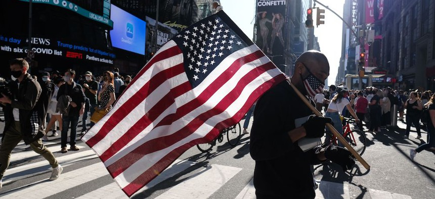 A man carries an American flag as people gather in Times Square in New York City to celebrate the election of Joe Biden as the 46th President of The United States.