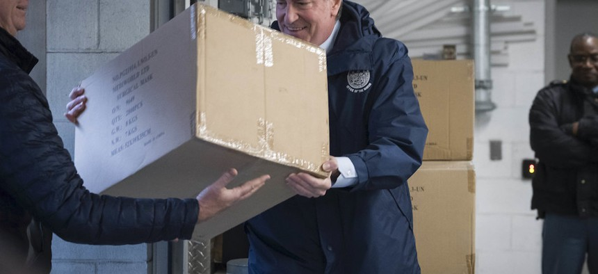 Mayor Bill de Blasio assists in picking up the United Nation's donation of 250,000 face masks.