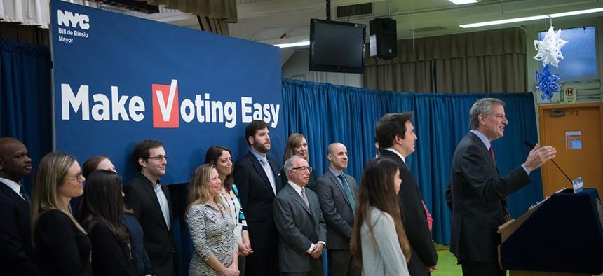 Mayor Bill de Blasio signs legislation to create a online voter registration system in December, 2017.