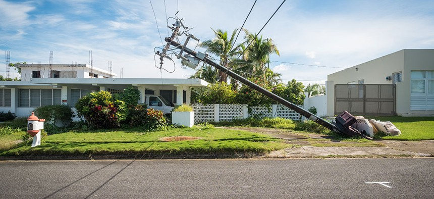 A broken telephone pole leans dangerously close to a house just outside of San Juan, Puerto Rico.