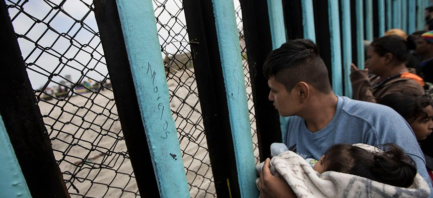 An asylum-seeking migrant from Central America holds a child while peering through the border wall in Tijuana, Mexico.