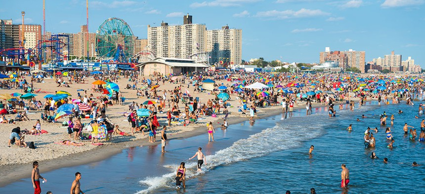 Crowds of people enjoying New York City's Coney Island beach in the midst of summer.