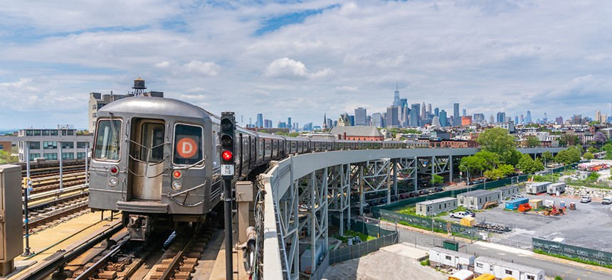 A D train entering the Smith St. station in Brooklyn with the Manhattan skyline in the background.
