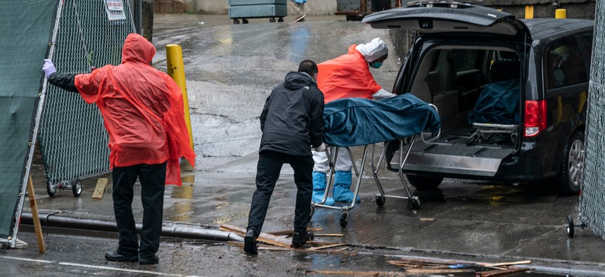 Funeral workers and hospital staff retrieve deceased bodies for burial amid COVID-19 pandemic at Brooklyn Hospital Center.