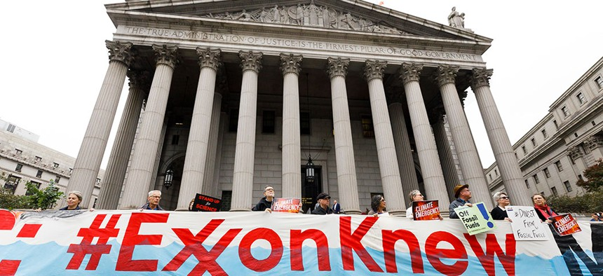 A group of protestors gathered outside of a New York City courthouse at the start of a legal case against Exxon Mobile.