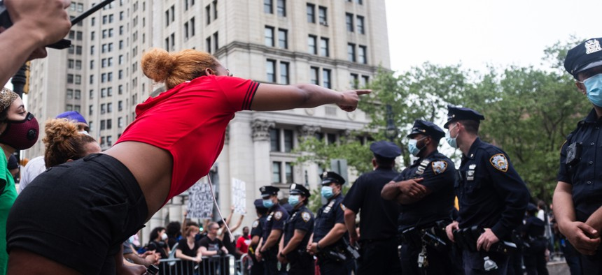 A young woman confronts police officers over a barricade at a protest over the death of George Floyd at the entrance to the Brooklyn Bridge. Jennifer M. Mason   Shutterstock