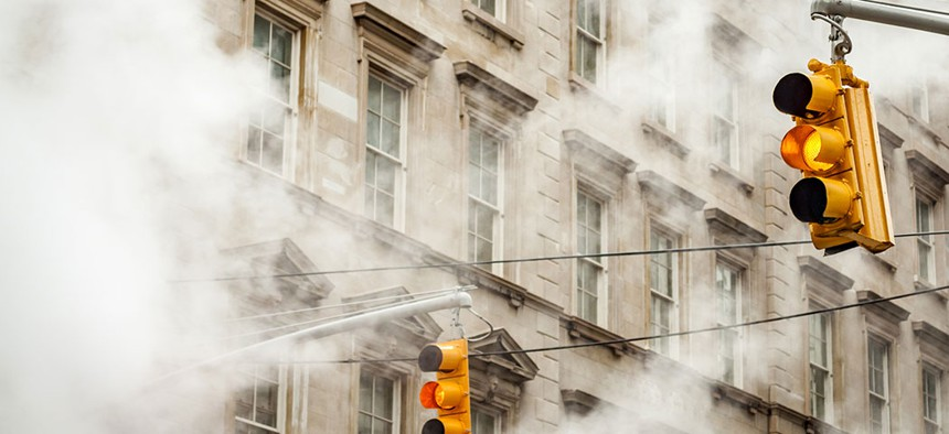 Traffic lights in New York surrounded by steam.