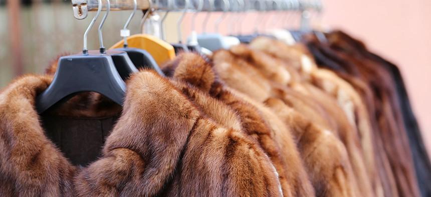 A clothing rack full of fur coats.
