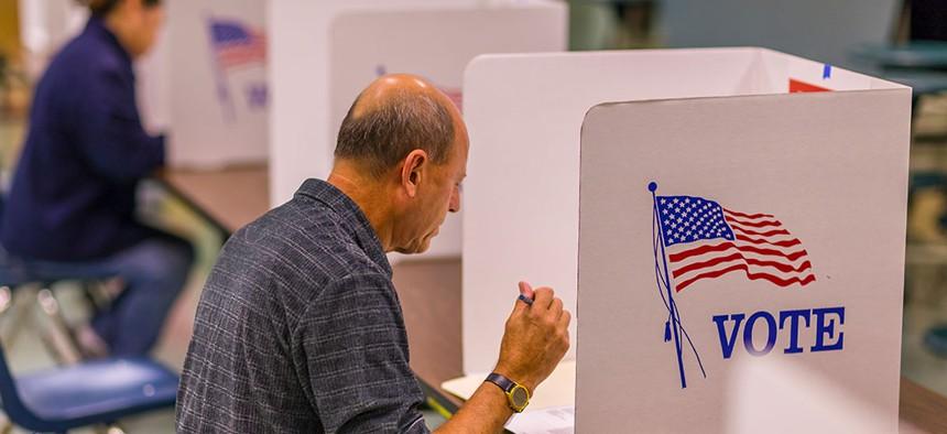 A civilian casts a vote.