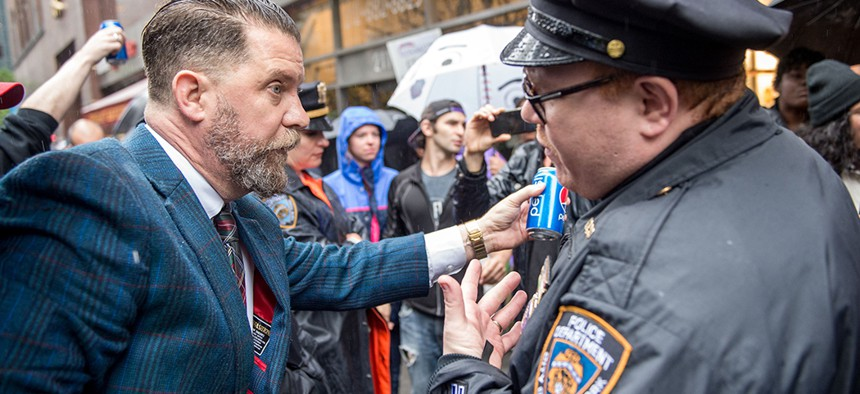 Gavin McInnes holds a pepsi can in front of an NYPD officer