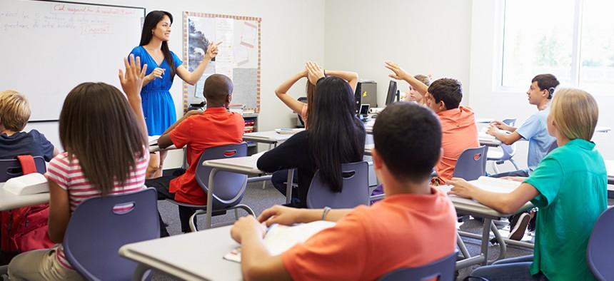Teacher addressing students in a high school classroom