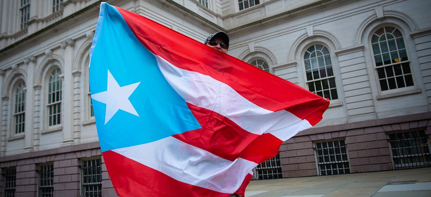 A man holds the Puerto Rican flag outside of New York City's City Hall.