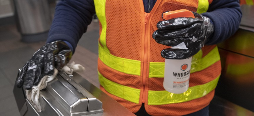 An MTA worker sanitizing the card reader.