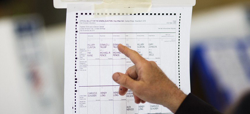 A voter looks over a sample 2016 New York ballot showing presidential candidates on multiple party lines.