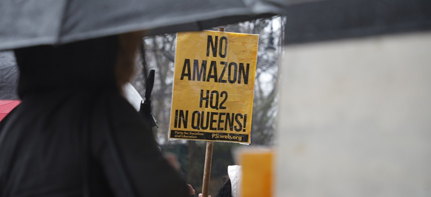 A protester holds a No Amazon HQ2 in Queens sign