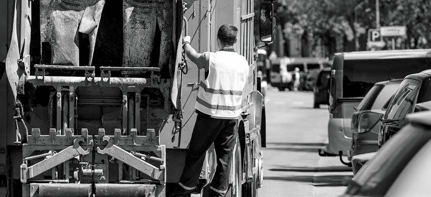 A man riding on the back of a garbage truck