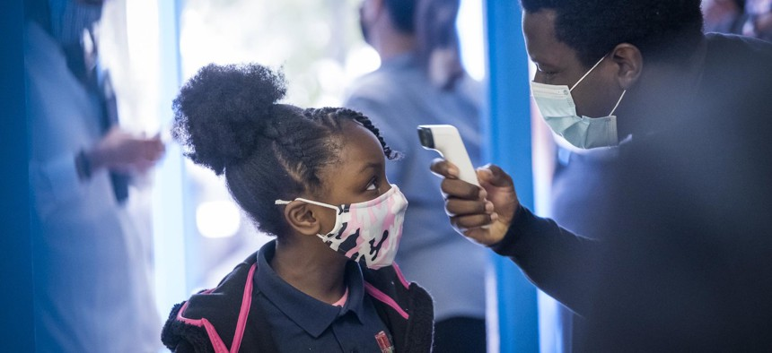 A NYC student getting her temperature checked as she walks into school on September 29th.