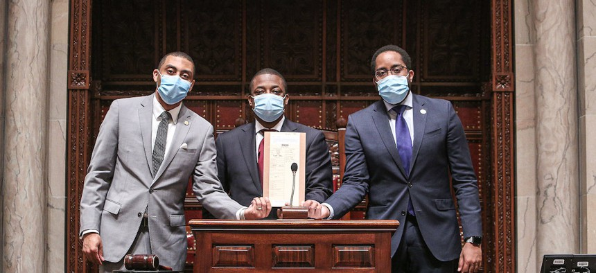 New York State Senators Jamaal Bailey, Brian Benjamin, and Zellnor Myrie holding the senate bill that repeals section 50-A.