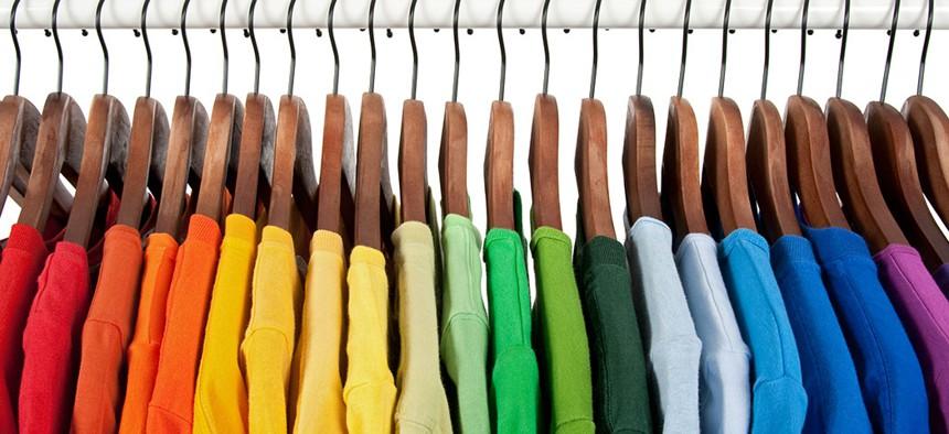 Rainbow shirts on a hanger.