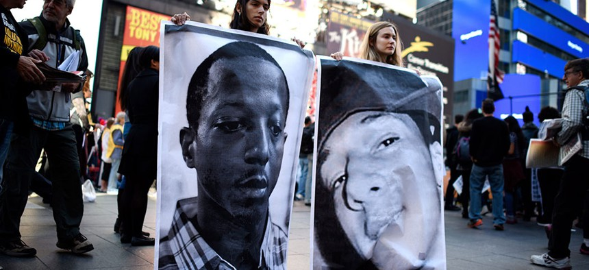 Photographs of Kalief Browder and Christopher Robinson — who both died as a result of alleged official misconduct related to Rikers Island Prison — are held up at a protest against police brutality.