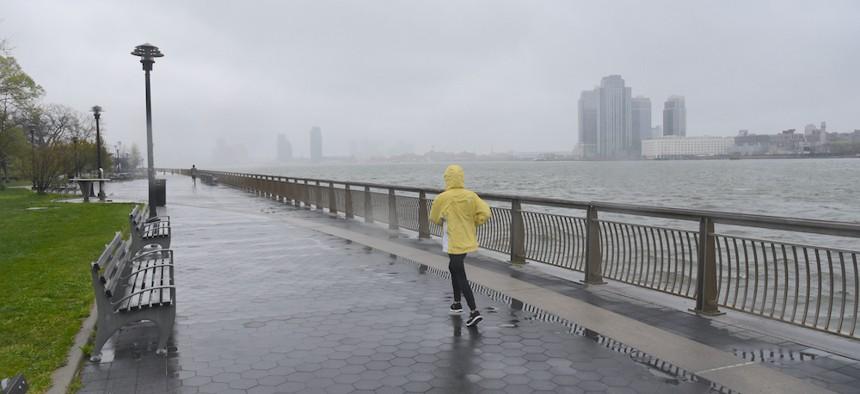 A Lone Jogger Jogs In The Rain Along John V. Lindsay East River Park