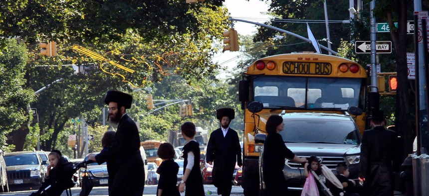 Orthodox Jewish children and adults cross a street in front of a school bus in Borough Park, Brooklyn.