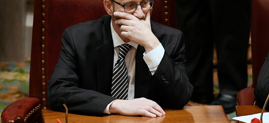 SImcha Felder holds his face in the  New York Senate Chambers.