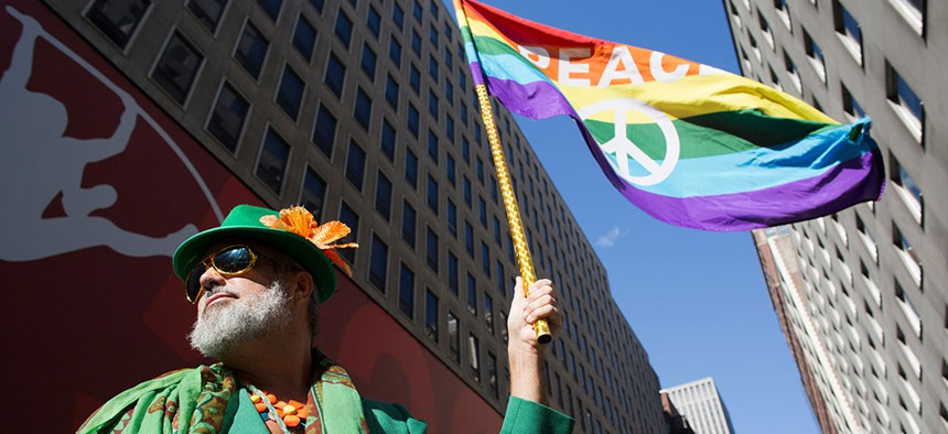Steven Menendez waves the Gay Pride flag as he waits for the St. Patrick's Day parade to begin in New York, 2016.