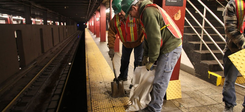 Platform tiles being replaced by MTA employees.