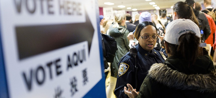 A police officers helps direct voters arriving to cast their ballots in the 2018 mid-term general election at a polling site in Brooklyn