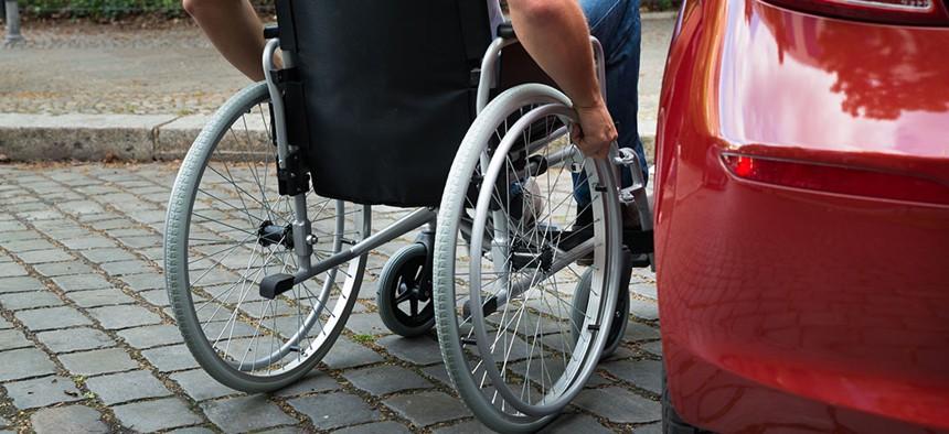 A wheelchair user getting into a car.