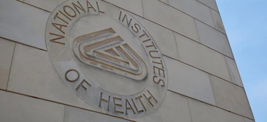 NIH NATIONAL INSTITUTES OF HEALTH sign emblem seal on gateway center entrance building at NIH campus.